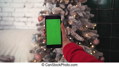 Girl holding a phone with a green screen on the background of the Christmas tree