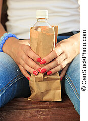 girl holding a plastic bottle in a paper bag