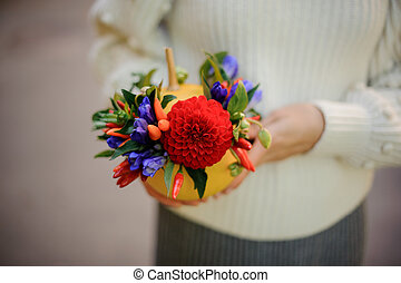 Girl holding a pumpkin decorated with red and blue flowers