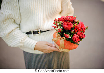 Girl holding a pumpkin decorated with red flowers
