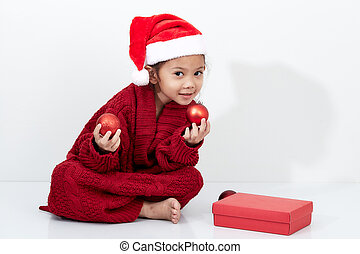 Girl holding a red christmas ball in sweater and santa hat