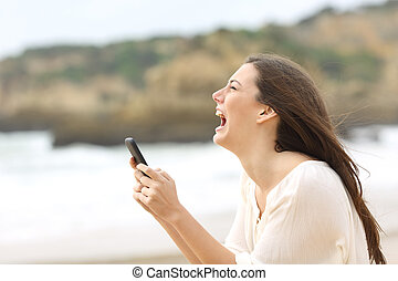 Girl holding a smart phone crying desperately - Side view of...