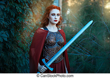 Beautiful girl holding a sword in his hand. She is an old-fashioned dress.