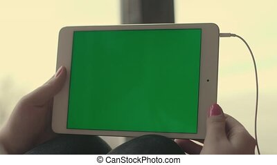 Girl holding a tablet with a green screen