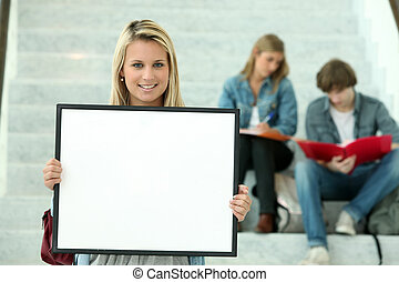 Girl holding a white board with students sitting in the background