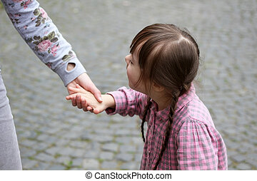 Girl holding arms of the mother on a walk
