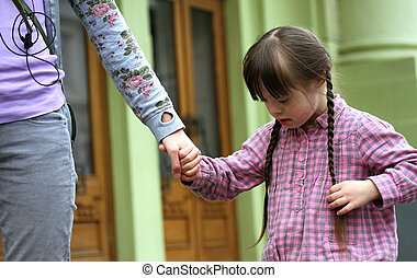 Girl holding arms of the mother on a walk .