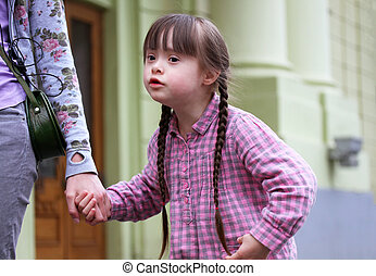Girl holding arms of the sister on a walk .