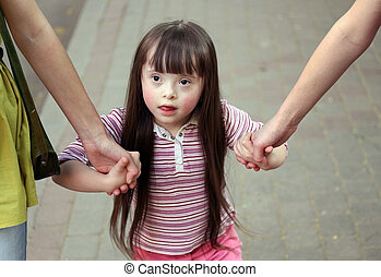 Girl holding arms of the sisters on a walk .