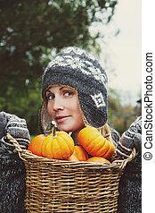 Girl holding basket of pumpkins