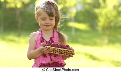 Girl holding basket of strawberries