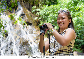 Girl holding binoculars in forest