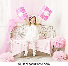 Girl holding birthday presents. Happy child with party gift box