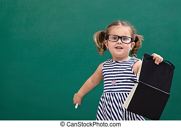 Girl Holding Book Standing In Front Of Chalkboard