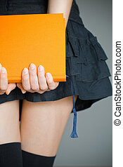 girl holding book - view of the lower body part of woman ...