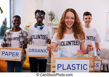 Girl holding box with plastic after sorting waste with friends