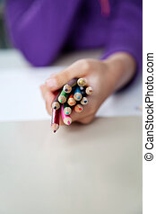 Girl Holding Bunch Of Colored Pencils At Desk