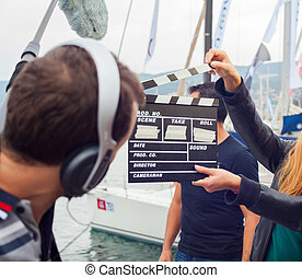 Girl holding clapperboard during the production of short...