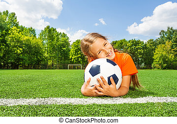 Girl holding close football, smiling and laying