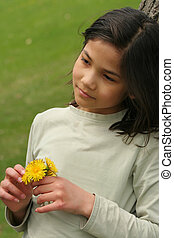 Girl holding dandelions with sad expression