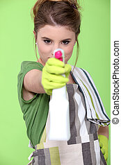 girl holding detergent with pistol pump against green...