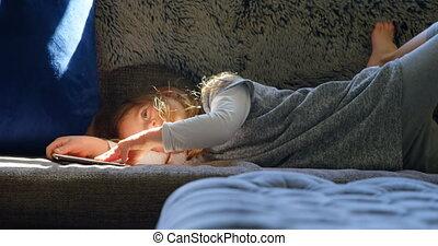 Girl holding digital tablet in living room 4k