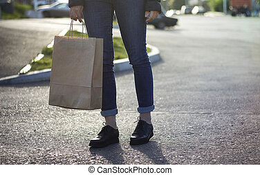 Girl holding ecological shopping with paper bag in hand.