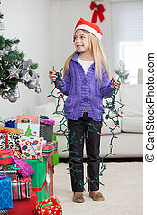 Girl Holding Fairy Lights While Standing By Christmas Gifts