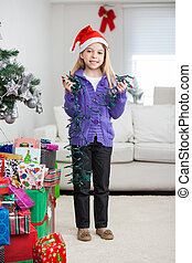 Girl Holding Fairy Lights While Standing By Christmas Presents