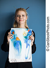 beautiful blonde girl holding watercolor sketches and smiling at camera isolated on blue