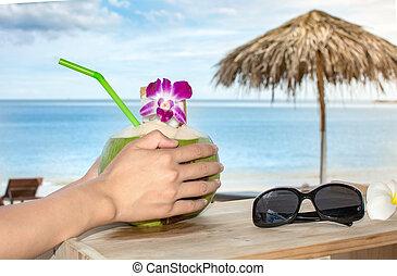 Girl holding fresh coconut at the beach resort