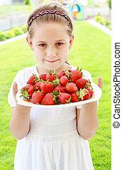 Girl holding fresh strawberries