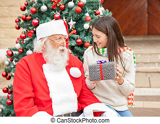 Girl Holding Gift While Looking At Santa Claus