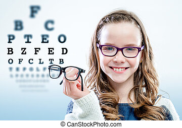 Girl holding glasses with test chart in background.