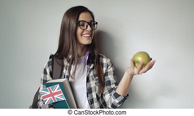 Student playing with an apple while holding a book and GB's flag