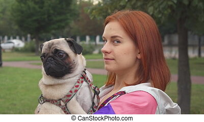 Girl holding her pug and smiling at camera