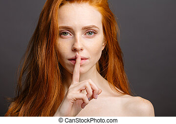 redhead girl with freckles holding index finger at her lips, quiet and shh gesture