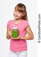 Girl holding jar tumbler mug with green smoothie drink -...