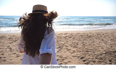 Girl holding male hand and running on beach to the ocean. Follow me shot of young woman in hat pull her boyfriend on the sea shore. Summer vacation or holiday concept. Point of view POV Slow motion