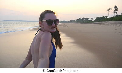 Girl holding male hand and running on tropical exotic beach...