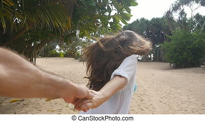 Girl holding male hand and running on tropical exotic beach to the ocean. Follow me shot of young woman pull her boyfriend on the sea shore. Summer vacation or holiday. Point of view. POV Slow motion