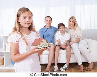 Girl Holding Miniature Model Of House