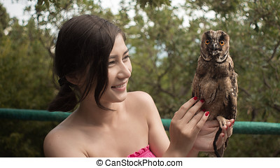girl holding on a hand of beautiful owl