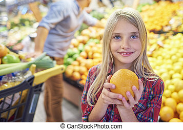 Girl holding orange in grocery store
