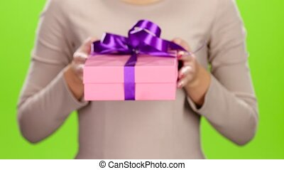 Girl holding out a box with a gift. Studio - Girl holding...