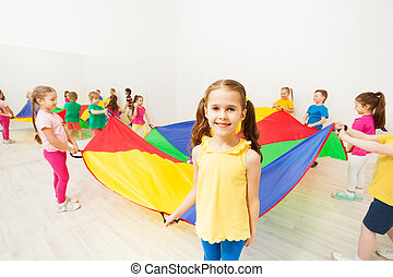 Girl holding parachute handle during funny game