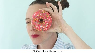 Girl holding pink donut looking through hole - Beauty...