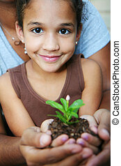 Girl Holding Plant - Girl with her mother holding a new...
