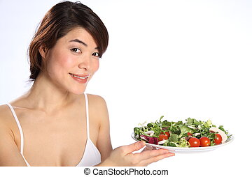 Girl holding plate of green salad