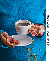 Girl holding poppy flowers and a White cup of warm morning coffee. Blue background.